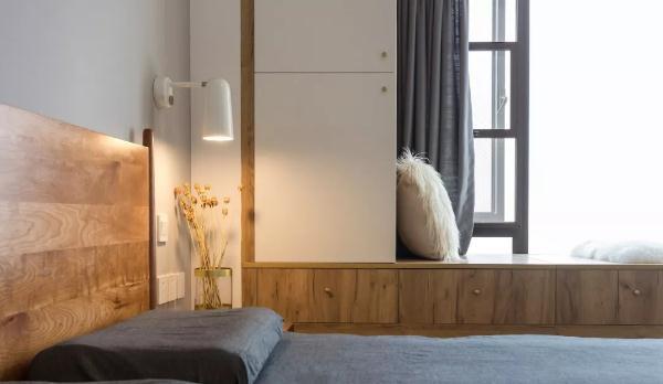 主卧地面通铺木地板,灰色床背景对称点缀阅读壁灯,床侧大衣柜,木色