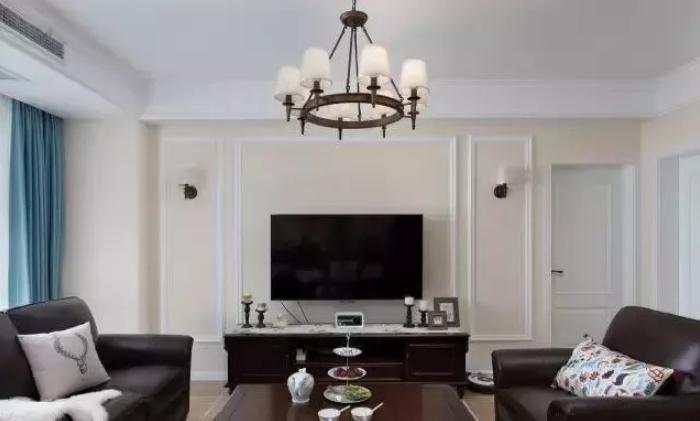 电视墙简单用石膏线做了造型,正中摆放电视机和电视柜,两侧各一盏壁灯