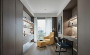 简约风格书房效果图,此书房的空间很小,家具颜色以浅棕色为主。一张简单的书桌与柜子连为一体,桌上放了一个插花玻璃,装饰效果很好。另外,靠窗的地方放置了单人沙发,累的时候可以在此休息。