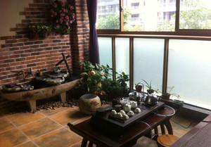 入户花园改茶室效果图,这里的入户花园茶室改造的可以说是非常复古了,深色的茶桌,加上深色的墙面色调,可以使整个入户花园变得很沉稳。