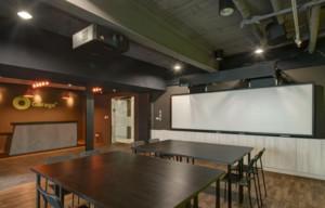 公司多功能会议室装修效果图,此公司多功能会议室的面积较大,会议桌是一张一张拼在一起的,为深棕色的木质桌子。其一面墙是完全的玻璃设计,可以直接看到公司内部其它空间。