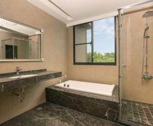 这个卫浴装修巧妙的运用了大理石,浴缸嵌入在大理石下面,台面也是用的大理石,使整体十分的协调,浴缸旁边是淋浴房,非常的节约空间。