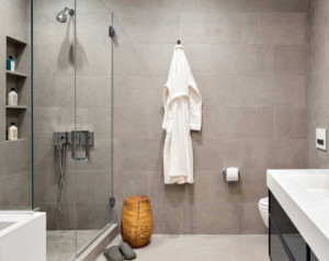 卫生间的面积在五六平米左右,玻璃隔开的淋浴房起到了很好的干湿分离效果,避免了在洗澡的时候水花乱溅。淋浴房借助墙面开凿出的置物架非常方便,还节省了空间。外面墙面安装几个挂钩,用来悬挂衣服。