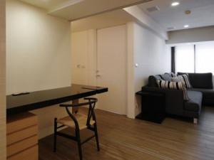 此吧台设计在客厅的一个角落,十分简约,仅为黑色的实木隔板靠墙安装,大大节约了居室空间。吧台的左下方一块区域摆放了抽屉式的柜子,可以用来收纳杂物。平时居住者坐在此处看看书、喝喝茶,非常惬意。